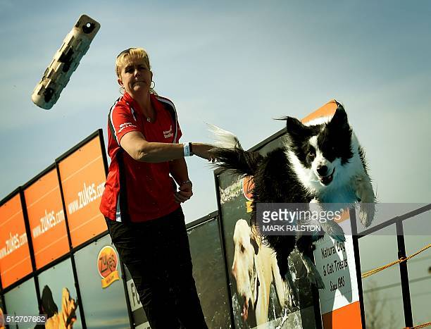 Whitney Lightner watches as her dog 'Saber' leaps into the water to record the distance of his jump during the Dock Dogs West Coast Challenge in...