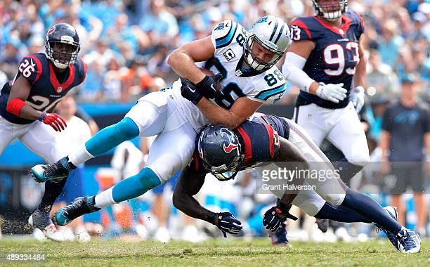 Whitney Mercilus of the Houston Texans tackles Greg Olsen of the Carolina Panthers in the third quarter during their game at Bank of America Stadium...