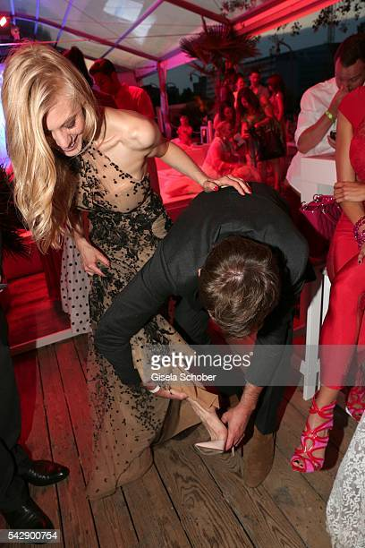 Whitney SudlerSmith helps his girlfriend Larissa Marolt into her shoe during the Raffaello Summer Day 2016 to celebrate the 26th anniversary of...