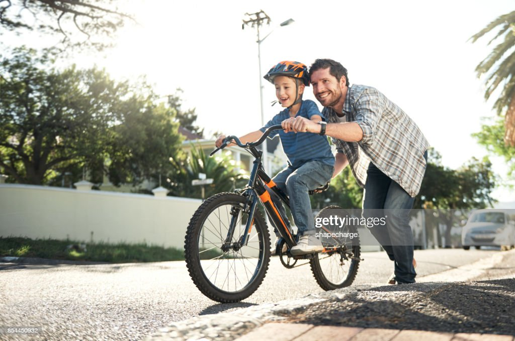 Who better to learn how to ride than with dad : Stock Photo