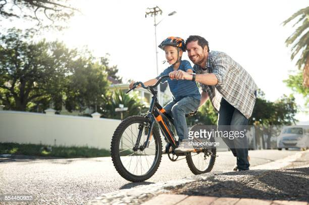 who better to learn how to ride than with dad - son stock pictures, royalty-free photos & images