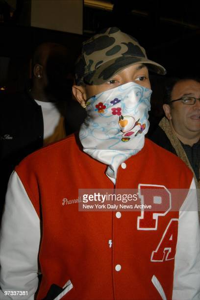 Who is that masked man It's Pharrell Williams and he's trying on or hiding behind a Louis Vuitton scarf at a Vuitton Fifth Ave store party