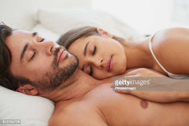 who needs a teddybear when you've got each other? - romantic young couple sleeping in bed stock photos and pictures