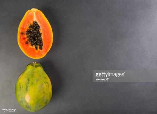 Whole and a half papaya on grey ground