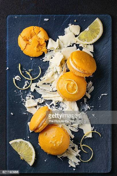 Whole and broken orange lemon homemade macaroons with chopped white chocolate and citrus sugar and zest on dark glass board over black textural background. Overhead view
