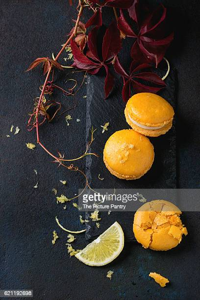 Whole and broken orange lemon homemade macaroons with white chocolate, lemon slice and zest, citrus sugar on slate board with autumn leaves over black textural background. Overhead view
