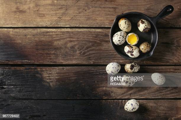 Whole and broken quail eggs with yolk in shell in small iron cast pan over old wooden plank background. Top view with space.