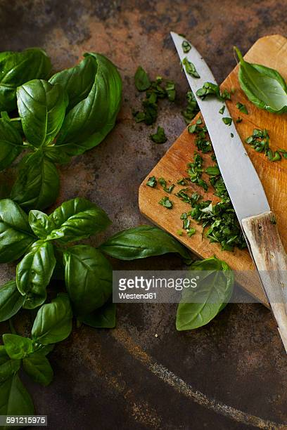 Whole and chopped basil leaves and kitchen knife on wooden board