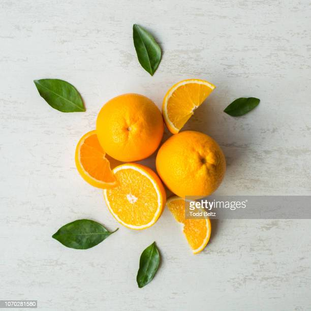 whole and cut oranges with the leaves from the orange tree on a white rustic background - ミカン ストックフォトと画像