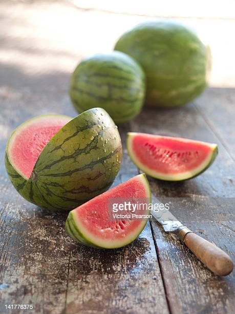 Whole and cut watermelon on wood table with knife.