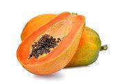 whole and half of ripe papaya fruit with seeds isolated on white background