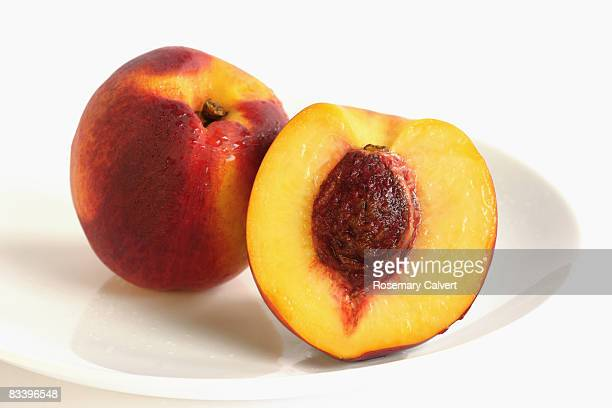 Whole and half peach on white background