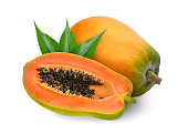 whole and half ripe papaya with green leaves isolated on white background
