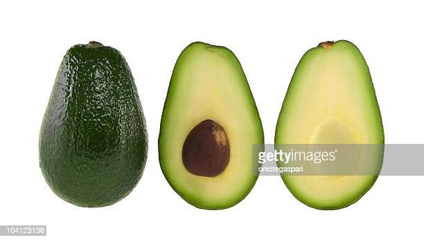 A whole and halved avocado on white