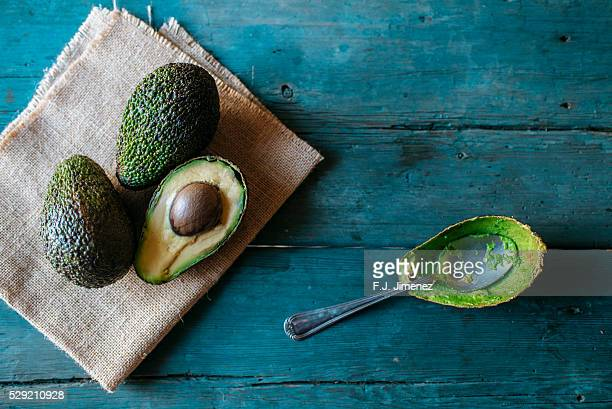 Whole and halved avocado on wooden table with spoon
