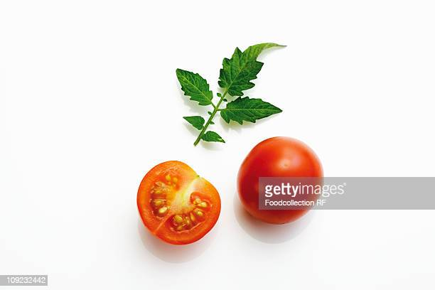 Whole and halved cocktail tomatoes with tomato leaf