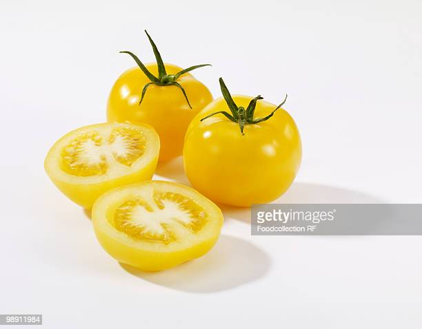 Whole and halved yellow tomatoes on white background, close-up