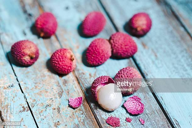 Whole and peeled lychee on lightblue wood