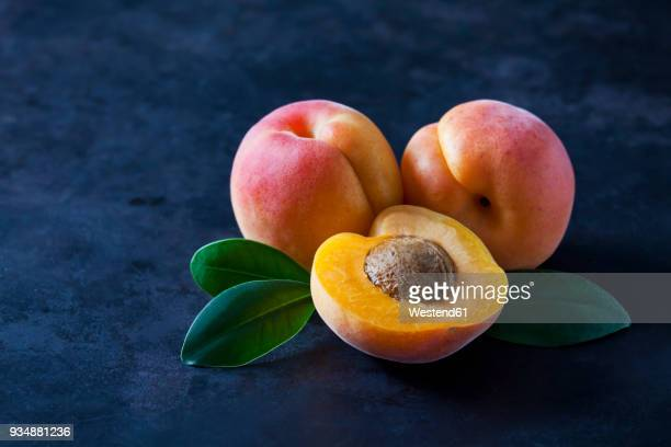 Whole and sliced apricots on dark ground
