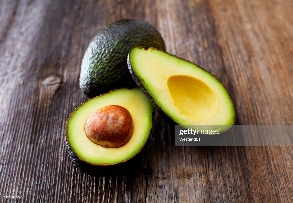 Whole and sliced avocado on wood : Stock Photo