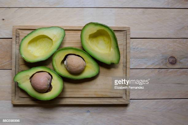 Whole and sliced avocado on wooden board