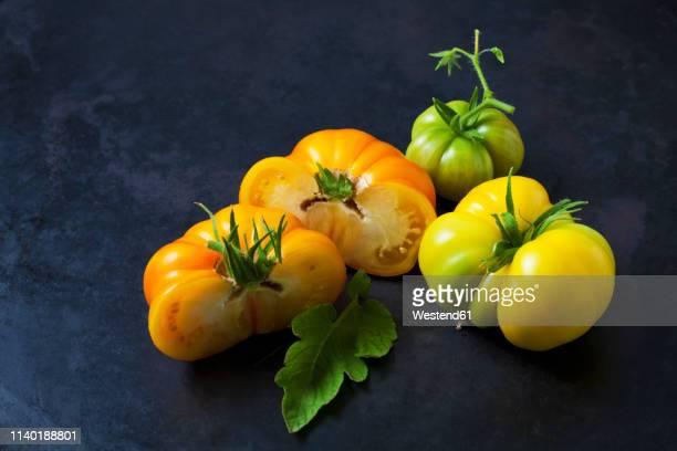 Whole and sliced Azoychka tomatoes on dark ground