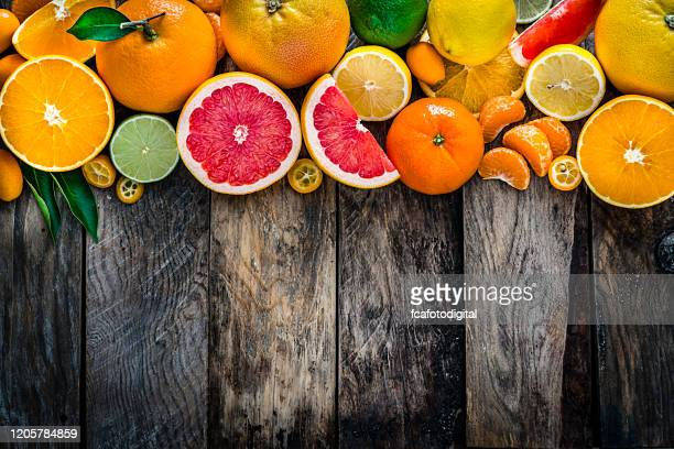 whole and sliced citrus fruits border on rustic wooden table - citrus fruit stock pictures, royalty-free photos & images
