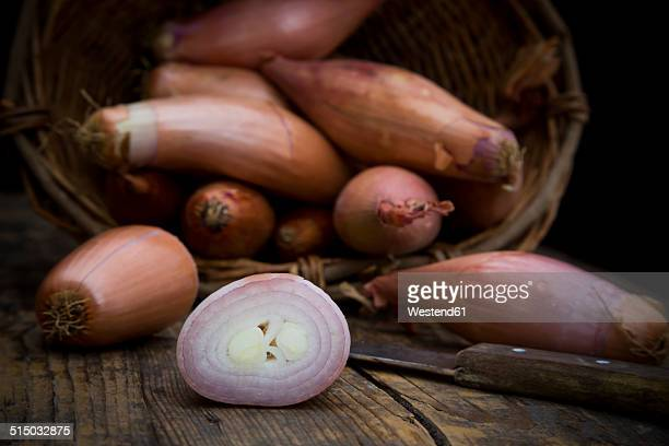 whole and sliced french banana shallots and kitchen knife on wood - echalote fotografías e imágenes de stock
