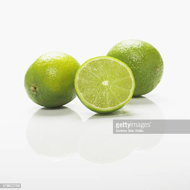 Whole and sliced fresh limes against white