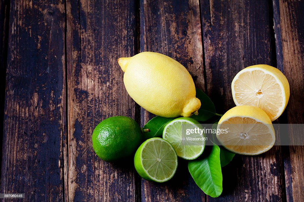 Whole and sliced lemons and limes on dark wood : ストックフォト