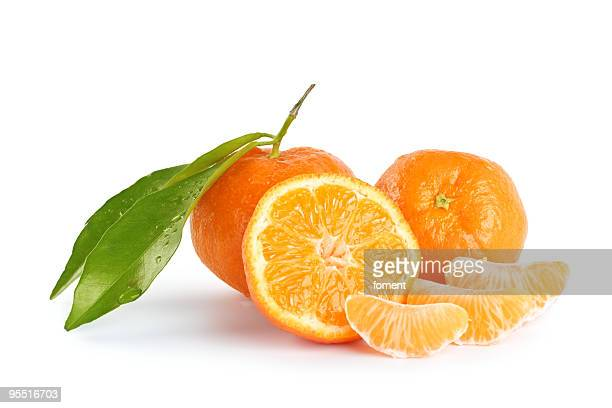 Whole and sliced mandarins on a white background