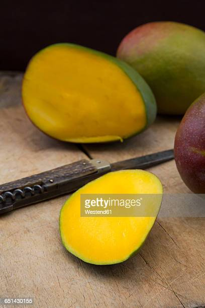 Whole and sliced mango and pocket knife on wood