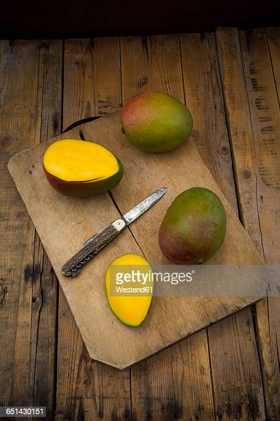 Whole and sliced mango and pocket knife on wooden board