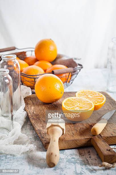 Whole and sliced orange, juice squeezer and knife on wooden board