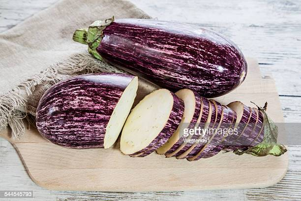 Whole and sliced organic aubergines on kitchen board