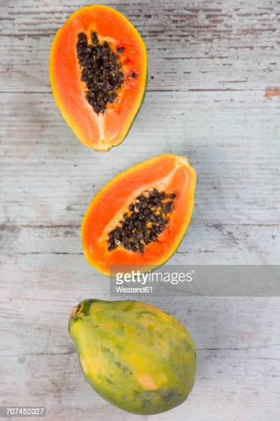 whole and sliced papaya on wood - papaya stock photos and pictures