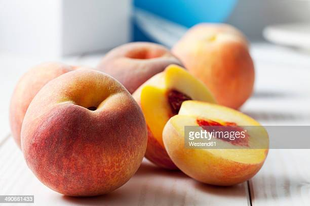 whole and sliced peaches (prunus persica) on white wooden table - perzik stockfoto's en -beelden
