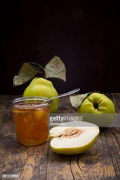Whole and sliced quinces and a glass of quince jam on wood