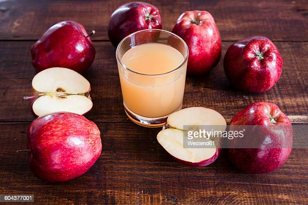 Whole and sliced red apples and a glass of apple juice on wood