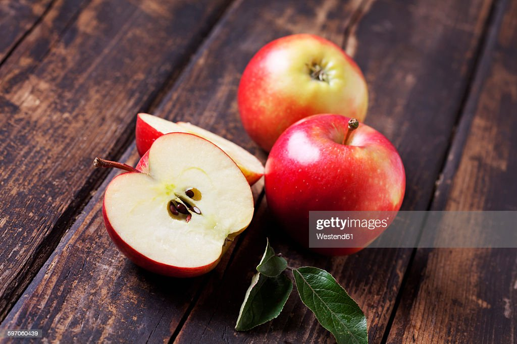 Whole and sliced red apples on dark wood : Stock Photo