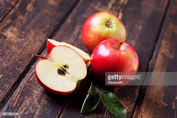 whole and sliced red apples on dark wood - apple event stock photos and pictures