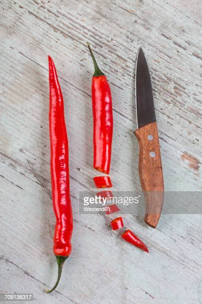 whole and sliced red chili pod and a kitchen knife on wood - red chili pepper stock pictures, royalty-free photos & images