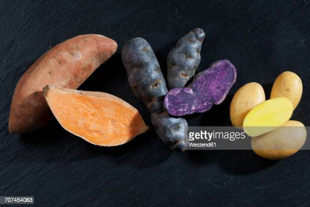whole and slices sweet potato, purple potato and drillinge on slate - prepared potato stock pictures, royalty-free photos & images
