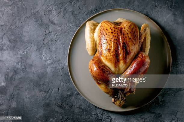 Whole baked chicken poultry on ceramic plate over black concrete background. Flat lay. Space. Dinner menu.