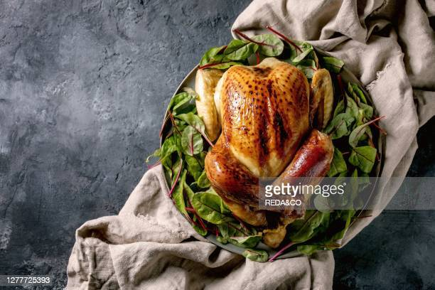 Whole baked chicken poultry on ceramic plate. Served with green beetroot salad leaves on linen cloth over black concrete background. Flat lay. Space....