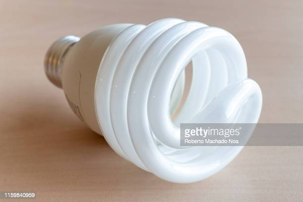 A whole compact fluorescent light bulb over a wood surface and illuminated with natural light