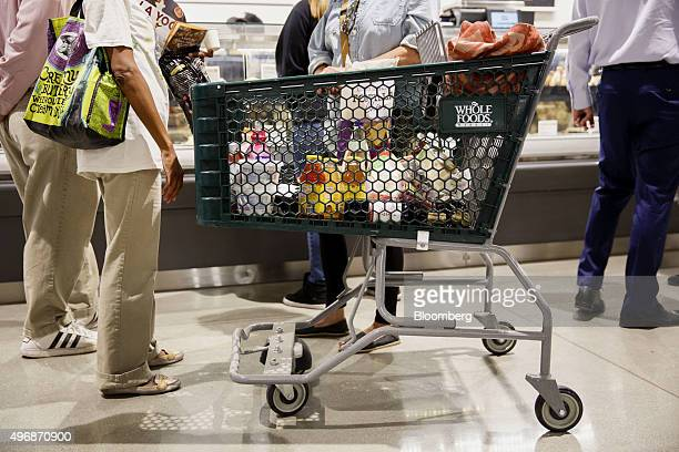 Whole Foods Market Inc signage is displayed on a shopping cart as customers browse the prepared foods section of the new store in downtown Los...