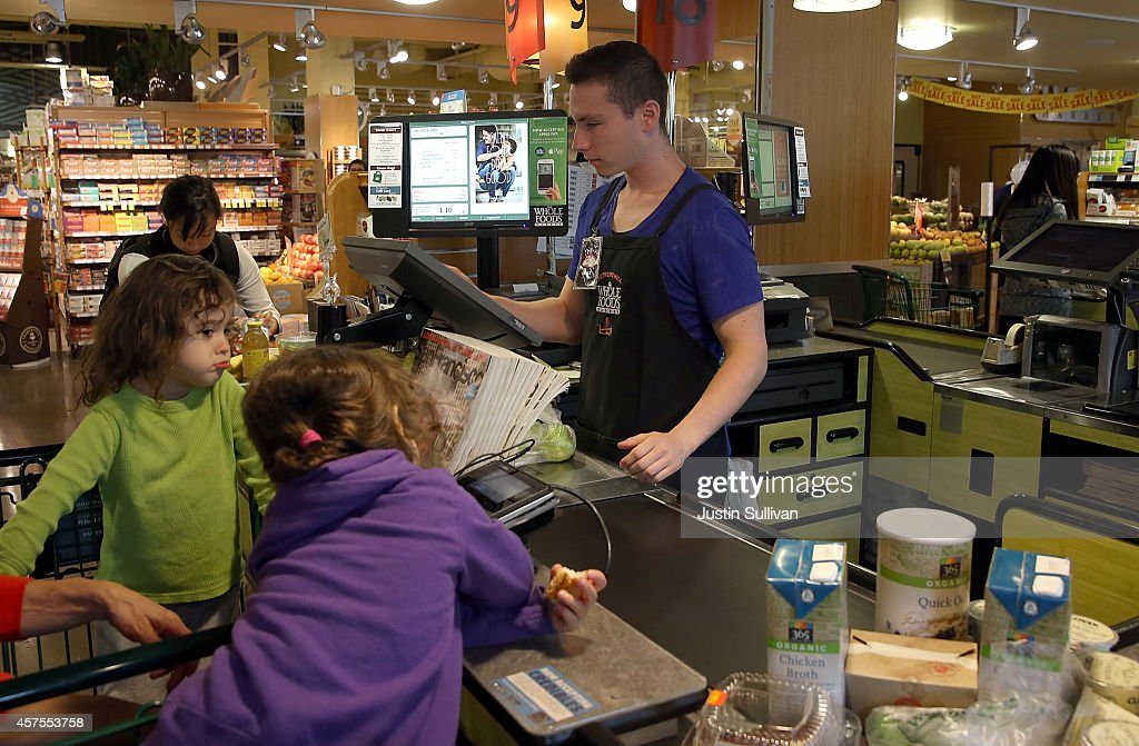 Whole Foods worker Max Koval rings up customers at a Whole Foods store on October 20, 2014 in San Francisco, California. Apple's Apple Pay mobile payment system launched today at select banks and retail outlets.