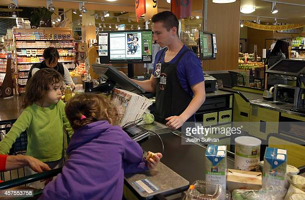 Whole Foods worker Max Koval rings up customers at a Whole Foods store on October 20 2014 in San Francisco California Apple's Apple Pay mobile...