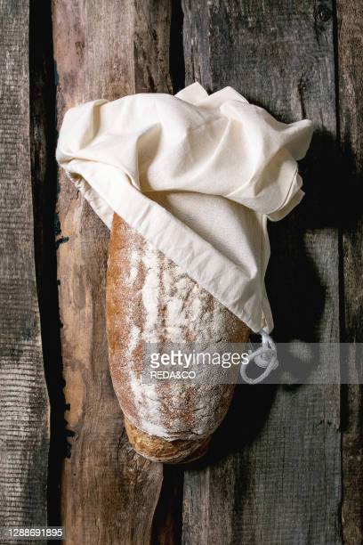 Whole grain fresh baked artisan rye-wheat organic bread from cotton textile bag over old wooden background. Flat lay, space.